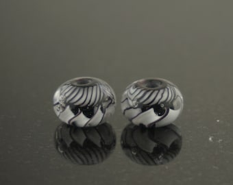 Pair of black and white  twistie and ribbon cane earring beads, encased.