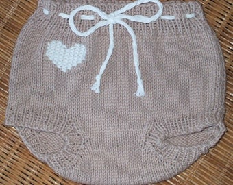 Hand knit diaper covers in tan 100% cotton and with a heart embroidered on them