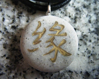 KARMA Japanese kanji symbol hand carved on a polymer clay grey granite color background.  Pendant comes with a FREE necklace
