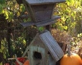 RESERVED :   Two rustic birdhouses attached to one post and an old twig.