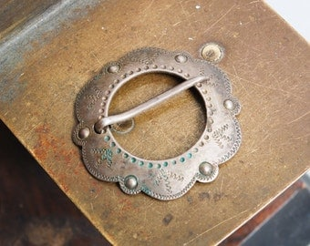 Vintage metal brooch styled as ethnic style penannular brooch.