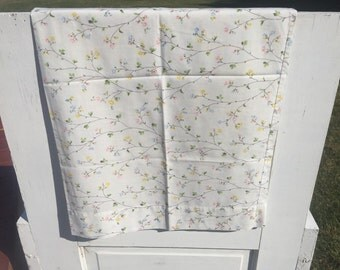 Vintage floral pillowcase with pink, yellow, and blue tiny flowers and green leaves