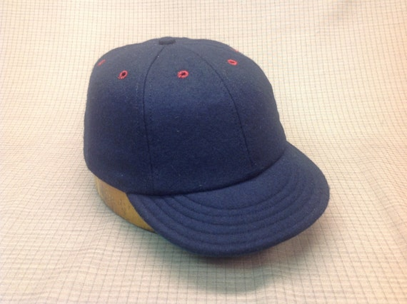 Custom made navy wool cap with burgundy eyelets and button. Any size available, fitted or adjustable.