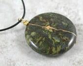 Kintsugi (kintsukuroi) dragon blood jasper round stone pendant with gold repair on black cotton cord - OOAK