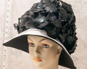 1970s white and black wool wide brimmed hat w black feathered crown.