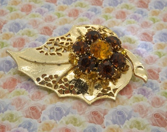 A beautiful large leaf and flower vintage jewelry brooch in goldtone openwork metal set with sparkly brown and amber faceted paste stones.
