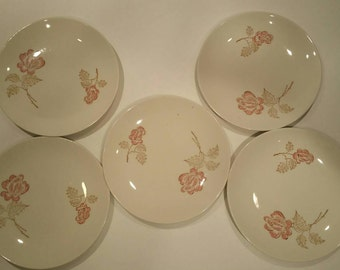 Five white china plates with roses.