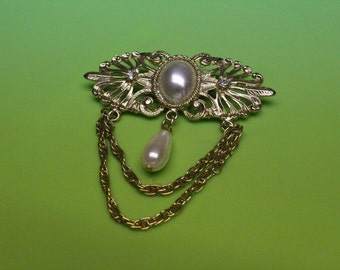 Gold tone brooch with faux pearl accent