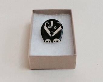 Small handmade pottery badger brooch.