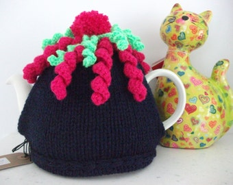 Tea cosy, hand knitted, navy blue with bright coloured spirals, topped with a bobble