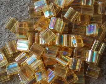 MIYUKI TILA Beads, 2 Hole, 5mm Square, Transparent Light Topaz AB , sold in units of approx 10gms.