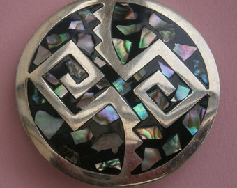 B581) A vintage silver tone metal and mother of pearl shell inlay Alpaca Mexico abstract pattern mosaic round pendant brooch.