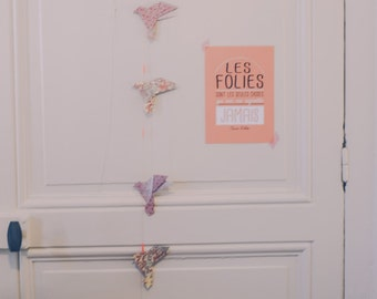 Origami garland of flying birds in orange and pink
