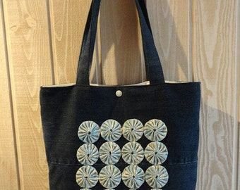 tote bag in recycled jean and yoyos (fabric flowers) pale blue background unbleached flowers