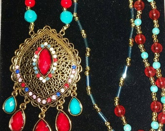 Gold tone ethnic style pendant on red and Turquoise beaded necklace