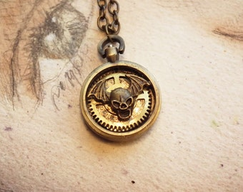 Small handmade Steampunk-gothic  pendant made of  pocket watchcase,  a skull and batwings gears   on a chain