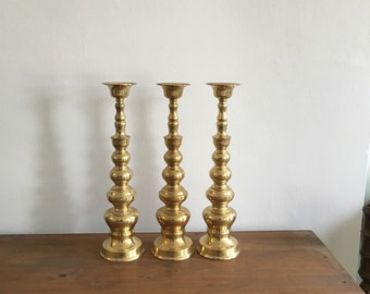 trio of large brass hollywood regency floor standing candle holders. vintage mid century wedding candlestick holders. boho interior design
