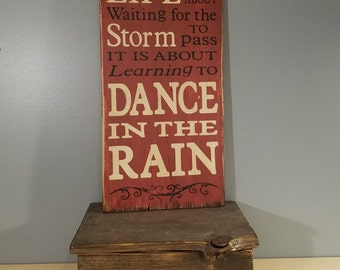 Life is not about waiting for the storms to pass, Dance in the Rain - Rustic Wooden Sign on Wood - .  Red with white and black lettering