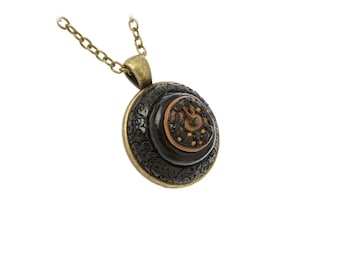 Watch-like pendant over antique bronze-color metal base.