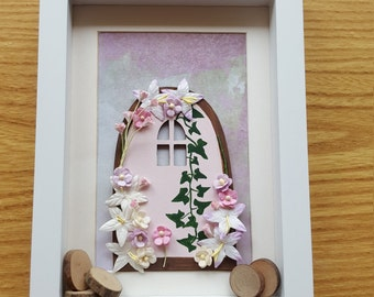 Fairy door box frame with flowers and log slices.