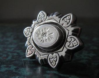 A vintage silver brooch  Victorian design with floral central lozenge and  6 heart shaped petals surrounding.