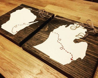 """State set: Two States hand painted on 10"""" by 10"""" wooden boards with hearts connected by dashed line."""