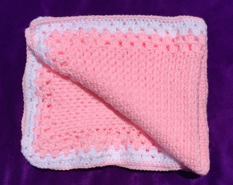 Pink crochet baby blanket with white trim