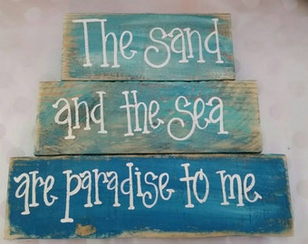 Weathered beach sign.  Sand and sea