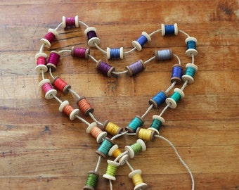 Colorful wood spool and thread garland