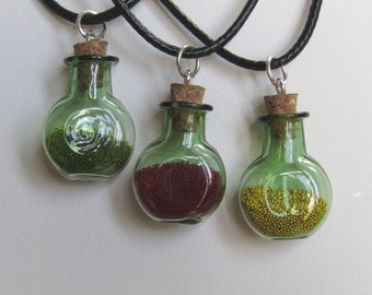 Green Glass Potion magic bottle necklace filled with micro beads on a faux leather cord. colours, red, green and gold effect