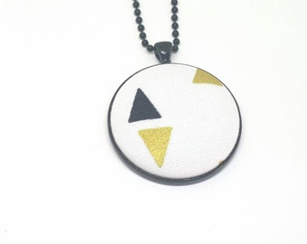 black and gold triangle fabric button on a black pendant