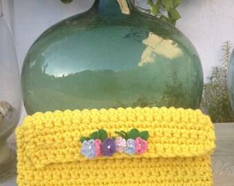 Clutch tejido a mano amarillo con detalle de flores