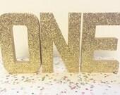 ONE - Gold Glitter letters { Stand Alone - 8in Paper Mache / cardboard }