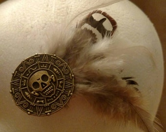 Pirate doubloons on feather hair clip.