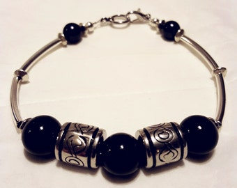 Black beaded bracelet with silver tube beads