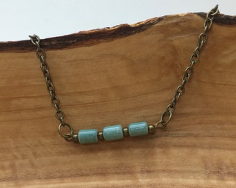 Cylinder shaped tiny everyday, turquoise color glass bead bar necklace.  Brass Antique Gold chain w lobster clasp.