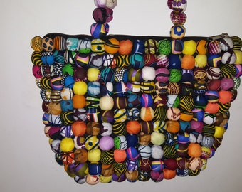 Handbag while balls of African fabrics.