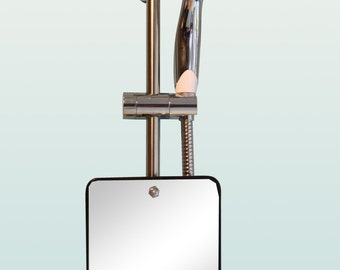 A polished stainless steel shower mirror