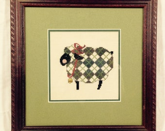 Framing of a sheep in an argyle coat, needle work