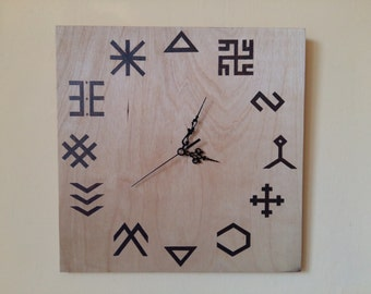 Wood wall clock with burned ancient latvian signs.