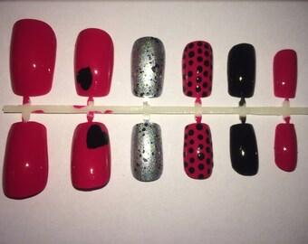 A set of handpainted false nails: pink nail with silver and black design and polka dots/pink nails/silver nails/black nails/polka dots nails