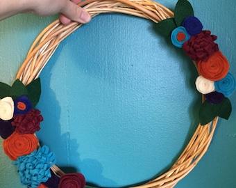 Handmade wicker wreath with colorful felt flowers