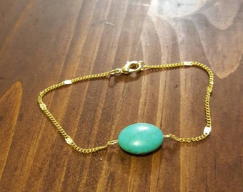Gold chain bracelet with turquoise charm