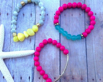 Stackable bracelets, neon pink, cross, yellow, blue and grey beads.