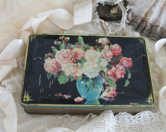 antique confectionery tin, bluebird toffee, pink roses, dramatic black background, fabulous timeworn patina of age, antique charm