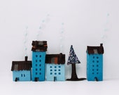 Four blue buildings of felt, with a tree. Miniature. Decoration.
