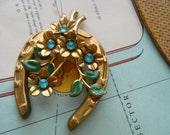 aqua rhinestone and enamel horseshoe and flower brooch in brass - vintage costume jewelry