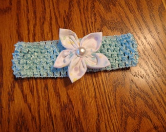 Infant headband in blue with pastel polk-a-dot fabric flower with pearl button center