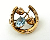 Vintage rolled gold lucky horseshoe brooch with pale blue stone