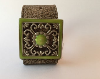 """Tan leather cuff featuring square buckle with green enamel. 1 1/2"""" wide fits up to 8 1/2"""" wrist"""